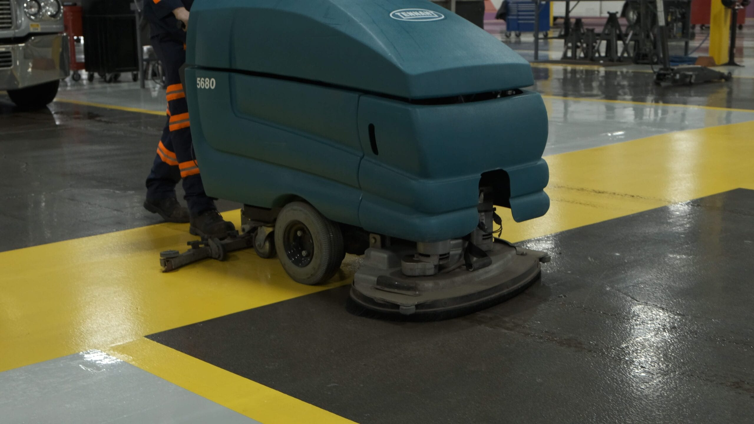 Employee cleaning floor in truck repair shop.