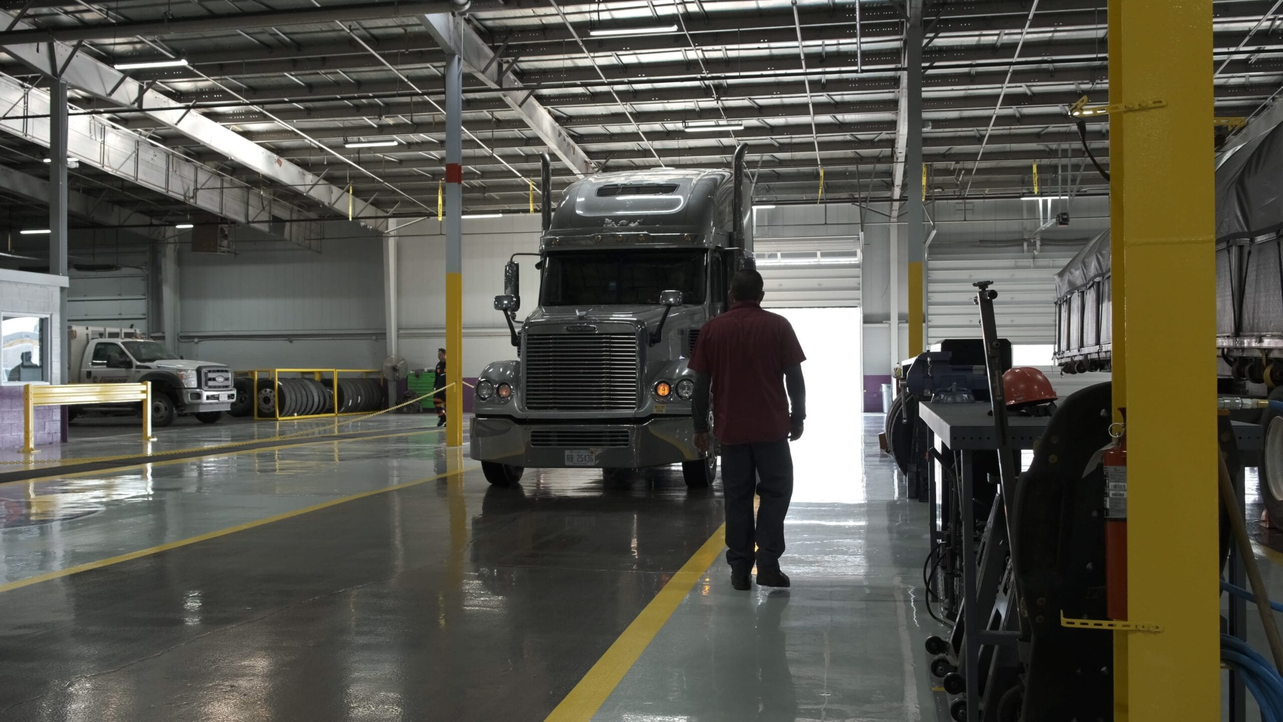 Semi truck pulling into a repair shop for service being greeted by an employee.