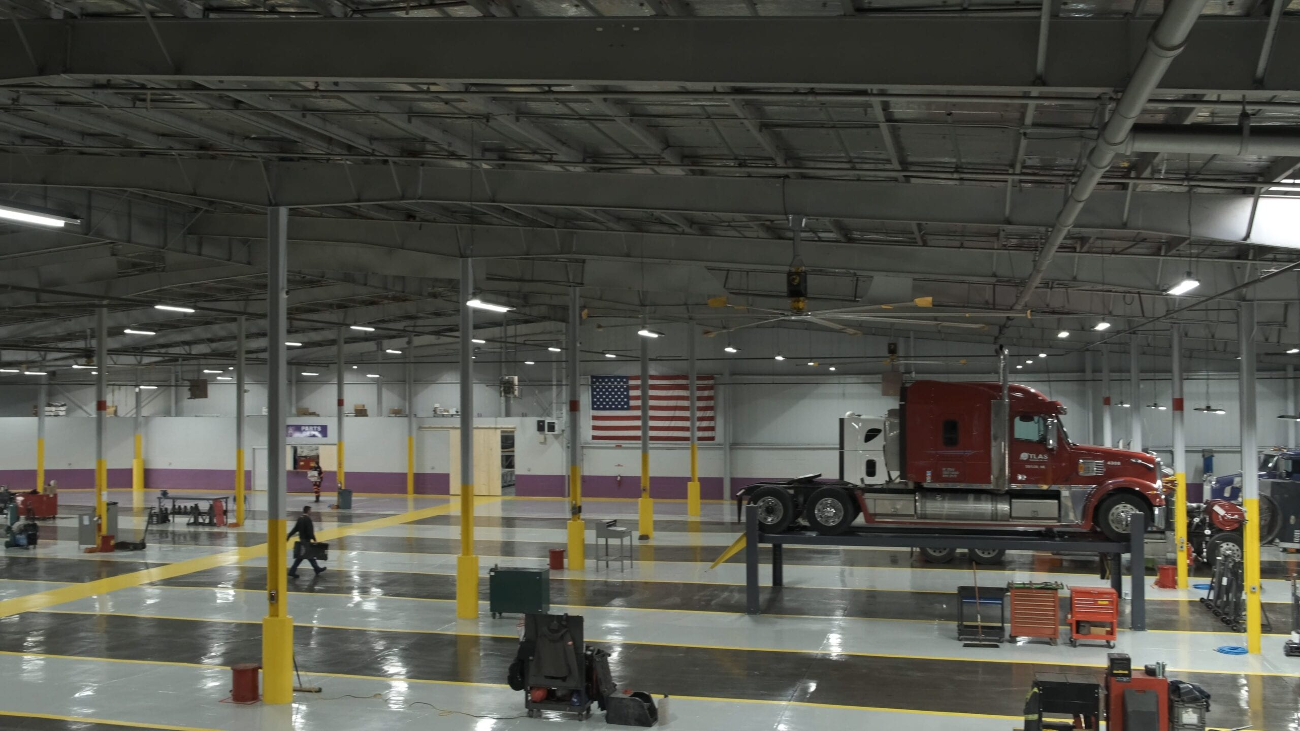 Interior of large semi truck repair shop with truck on a lift and American flag on the wall in the background.